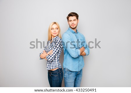 Young angry couple in love standing back to back - stock photo