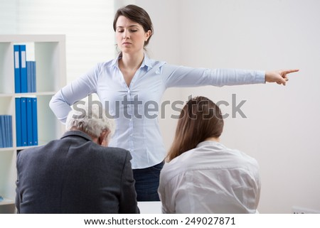Young angry employer throwing two employees out of the door - stock photo
