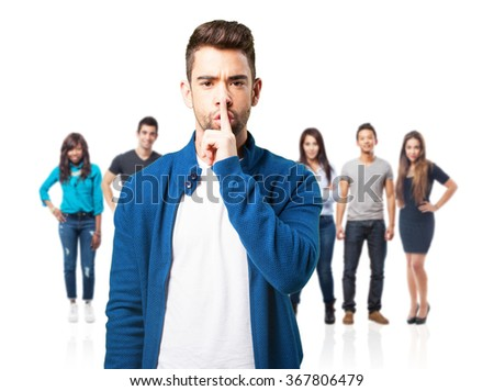 young angry man doing a silence gesture - stock photo