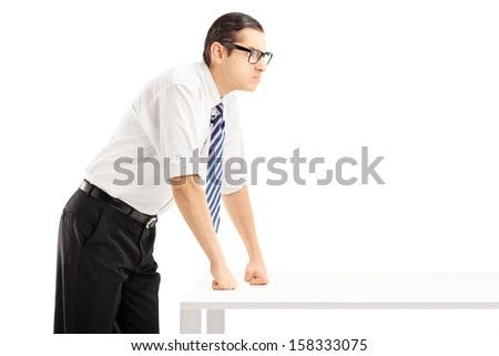 Young angry man on a table isolated on white background - stock photo