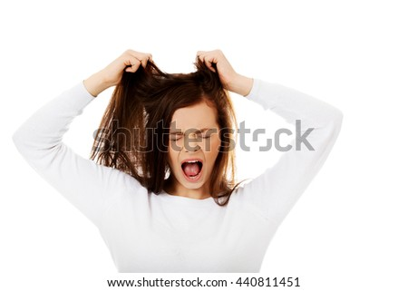 Young angry woman pulling her hair - stock photo