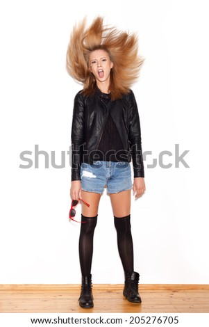 Young angry woman shaking her hair . White background, not isolated - stock photo