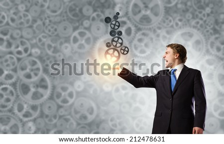 Young anxious businessman holding gears in palm