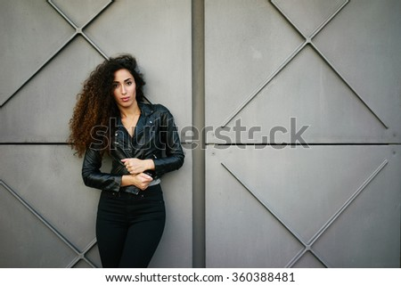 young appealing girl with a good figure and long curly hair against a background of gray concrete wall with copy space area for your text or design - stock photo