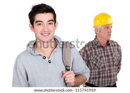 young apprentice posing next to craftsman - stock photo