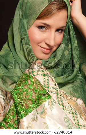 Young arab woman with veil close-up portrait on dark background