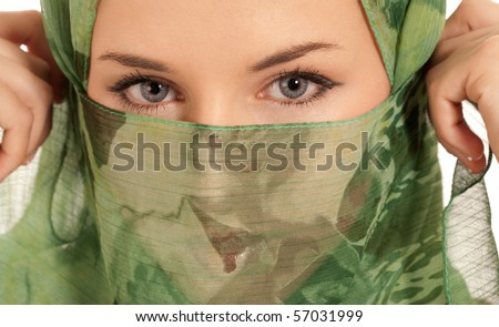 Young arab woman with veil showing her eyes isolated on white background.