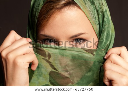 Young arab woman with veil showing her eyes on dark gray background