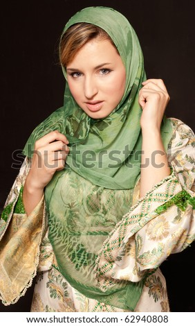 Young arab woman with veil standing on dark background - stock photo