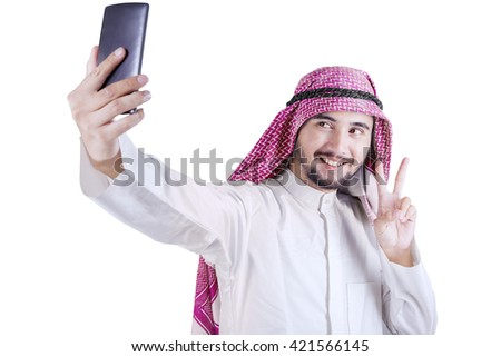 Young Arabian person taking selfie picture with a smartphone in the studio, isolated on white background