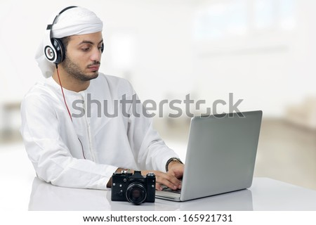 Young Arabian photographer working on his Laptop - stock photo