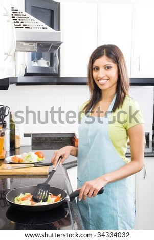 young arabian woman cooking in kitchen - stock photo