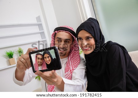 Young Arabic Couple Taking Selfie At Sofa - stock photo