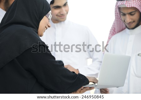 Young Arabic Muslim business woman leading group of Middle eastern Gulf guys - stock photo