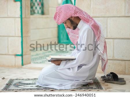 Young Arabic Muslim man reading Koran and praying - stock photo