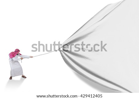 Young Arabic person wearing traditional clothes and pulling a big banner in the studio