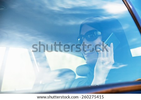 Young Arabic Woman In Car Having Phone Conversation - stock photo