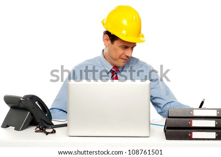 Young architect actively working at his desk. Indoor studio shot - stock photo