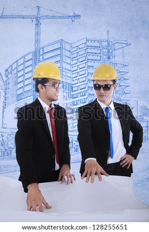 Young architect and supervisor are reviewing plans over blueprints background - stock photo