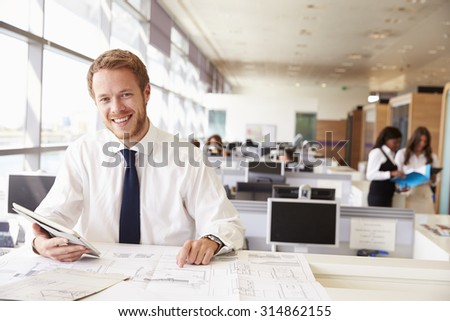 Young architect at work in an office, smiling to camera - stock photo