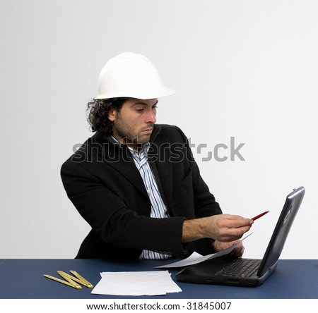 Young architect at work with laptop - stock photo