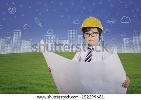 Young architect boy holding plan outdoor - stock photo