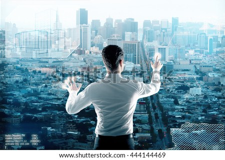 Young architect building city on digital interface - stock photo