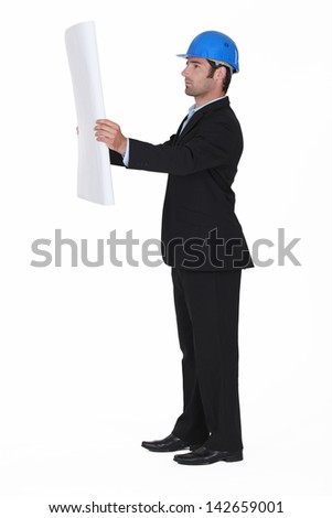 young architect in profile consulting blueprints - stock photo