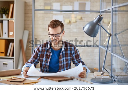 Young architect looking at blueprint in office - stock photo