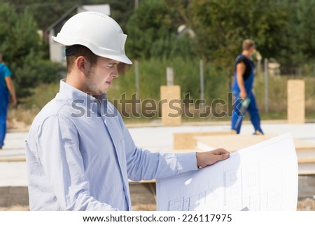 Young architect or engineer checking specifications on a plan or blueprint as he stands overlooking the construction site - stock photo