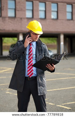 young architect or inspector with office building as blurred background, talks over his mobile phone - stock photo