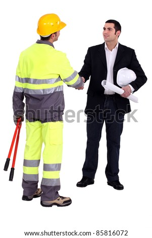 young architect shaking hands with craftsman - stock photo