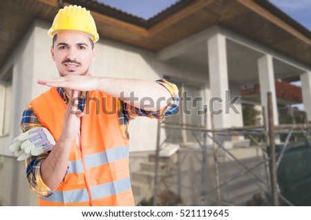 Young architect standing outside on building site and doing timeout or pause gesture with copy space area