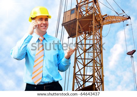 Young architect wearing a protective helmet standing on the building background - stock photo