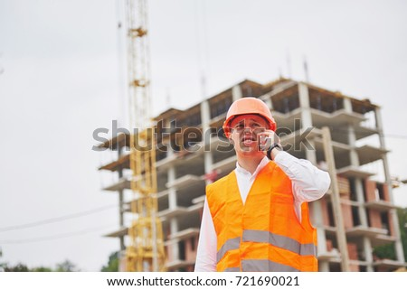 Young architect wearing a protective helmet standing on the mountains building outdoor background.
