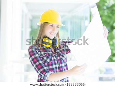 Young architect whit earmuffs, helmet and construction plans