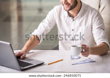 Young architect with blueprint is drinking coffee while siting in the office. - stock photo