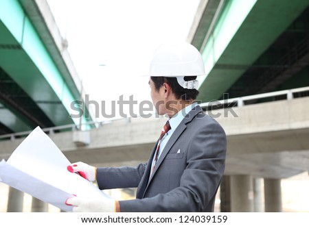 young architect  with blueprint on highway construction site