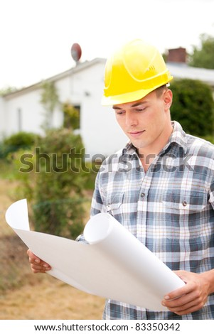 Young architect with plan in front of a building