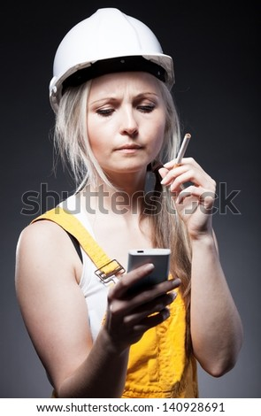 Young architect woman construction worker smoking cigarette and holding phone
