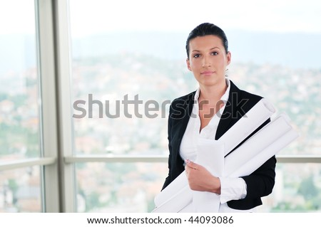 young architect woman in business suit portrait with blueprints