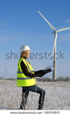 Young architect-woman wearing protective winter cloth standing against wind turbines - stock photo