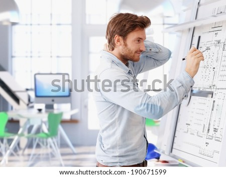 Young architect working at drawing board, thinking. - stock photo
