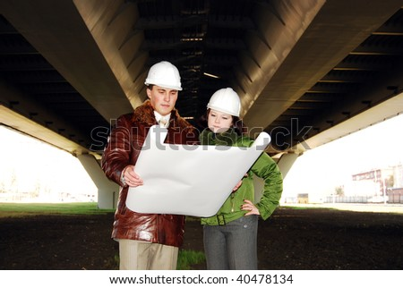 Young architects looking at blueprint. - stock photo