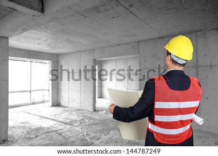 Young architects looking at blueprint in front of construction site - stock photo