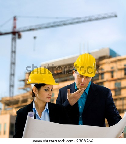 Young architects looking at blueprint in front of construction site, building and crane. - stock photo