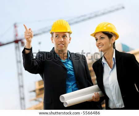 Young architects wearing a protective helmet standing in front of a building site. - stock photo