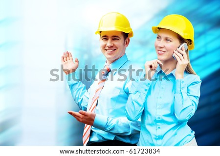 Young architects wearing a protective helmet standing on the building background - stock photo
