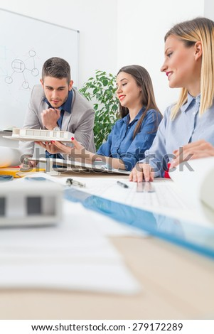 Young architects working on their design showing models and plans - stock photo