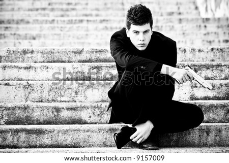 Young armed gun waiting on the steps - stock photo